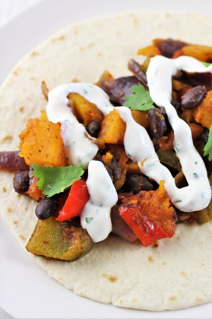roasted vegetables topped with cilantro lime cream on a flour tortilla