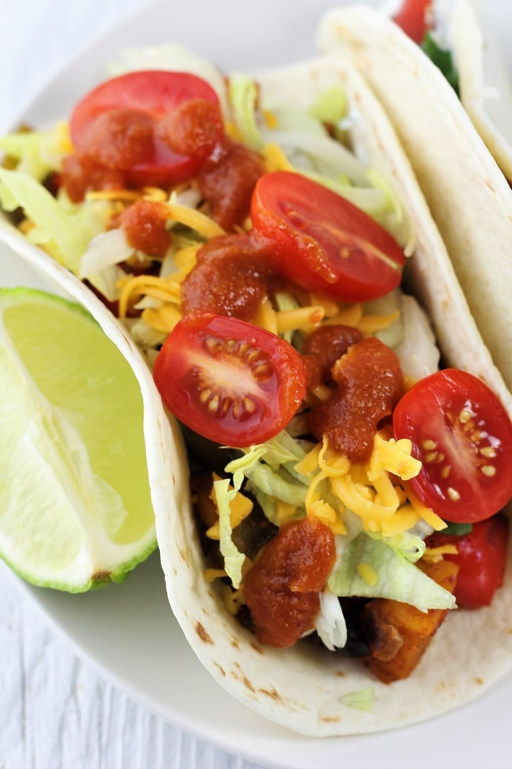 roasted veggie taco topped with lettuce, cheese, taco sauce, and tomatoes with a lime wedge