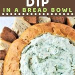 bread bowl filled with dip with bread cubes around it with a text overlay that says now cook this spinach dip in a bread bowl