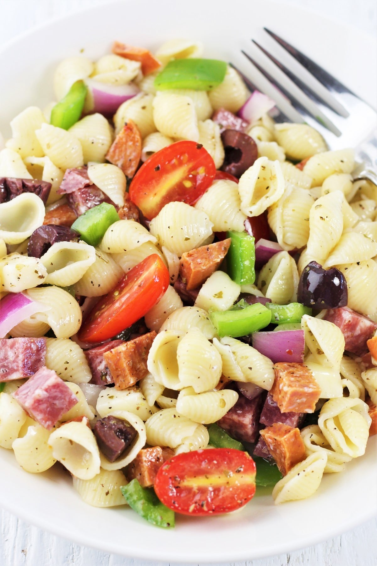 antipasto pasta salad in a white bowl with a fork