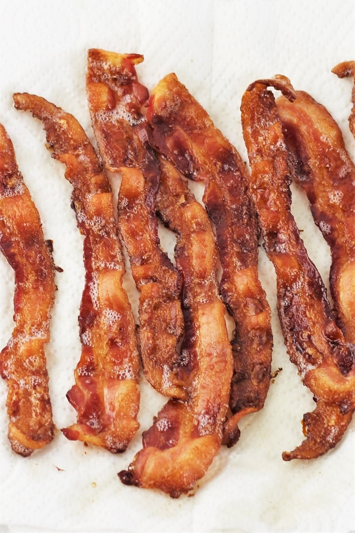 several strips of cooked bacon on a white plate