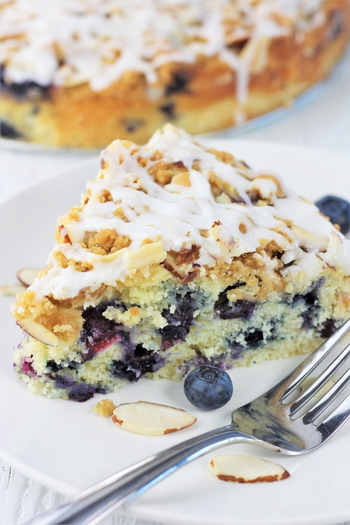 piece of blueberry almond coffee cake on a white plate with a fork with the whole cake in the background