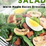 spinach salad on a plate with a fork with a text overlay that says now cook this spinach salad with warm maple bacon dressing