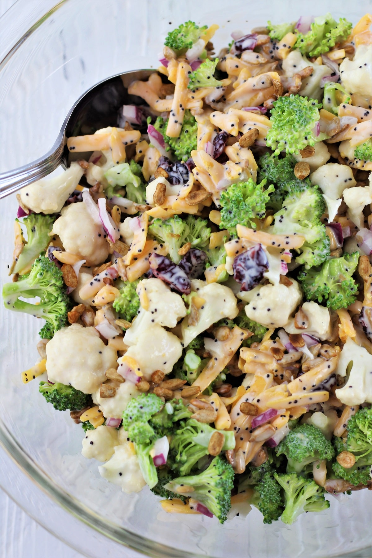 bowl full of broccoli and cauliflower salad with a serving spoon