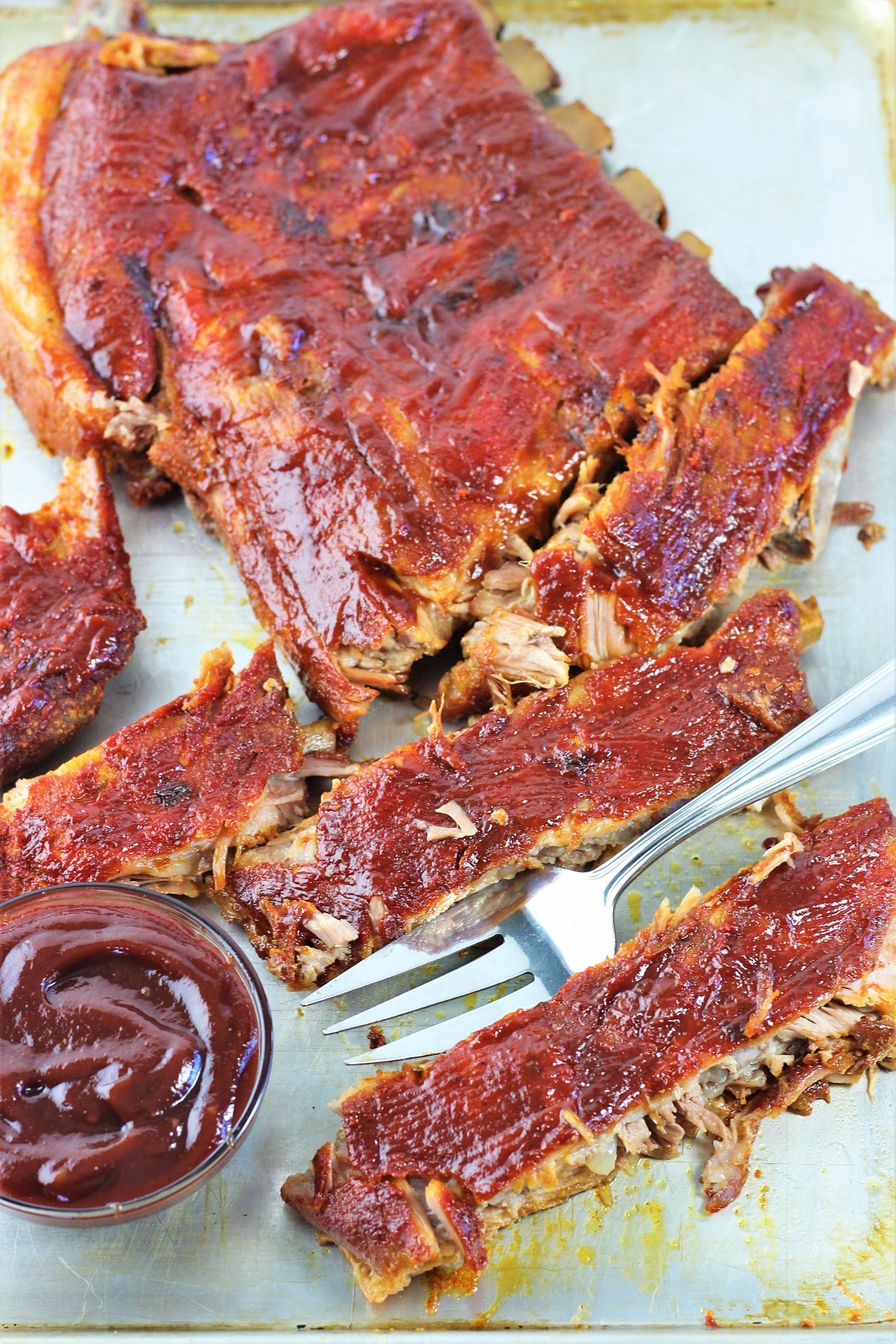 bbq pork ribs on a serving tray with a serving fork and a small bowl of barbecue sauce