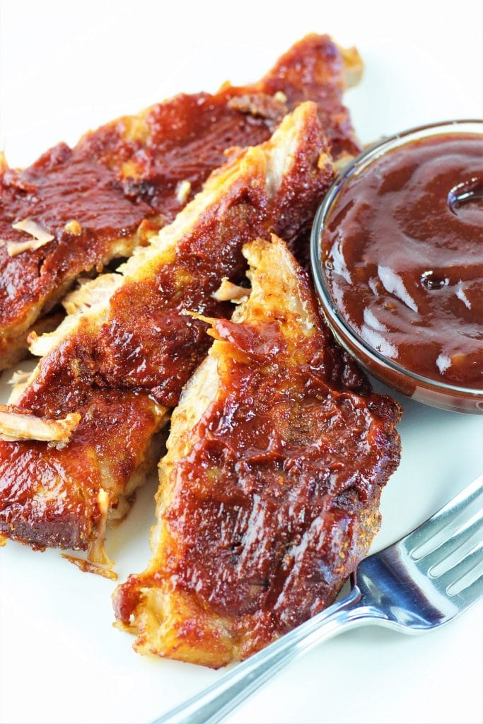 pork ribs on a plate with a fork and a small bowl of barbecue sauce