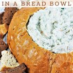 spinach dip in a bread bowl with a text overlay that says spinach dip in a bread bowl nowcookthis.com