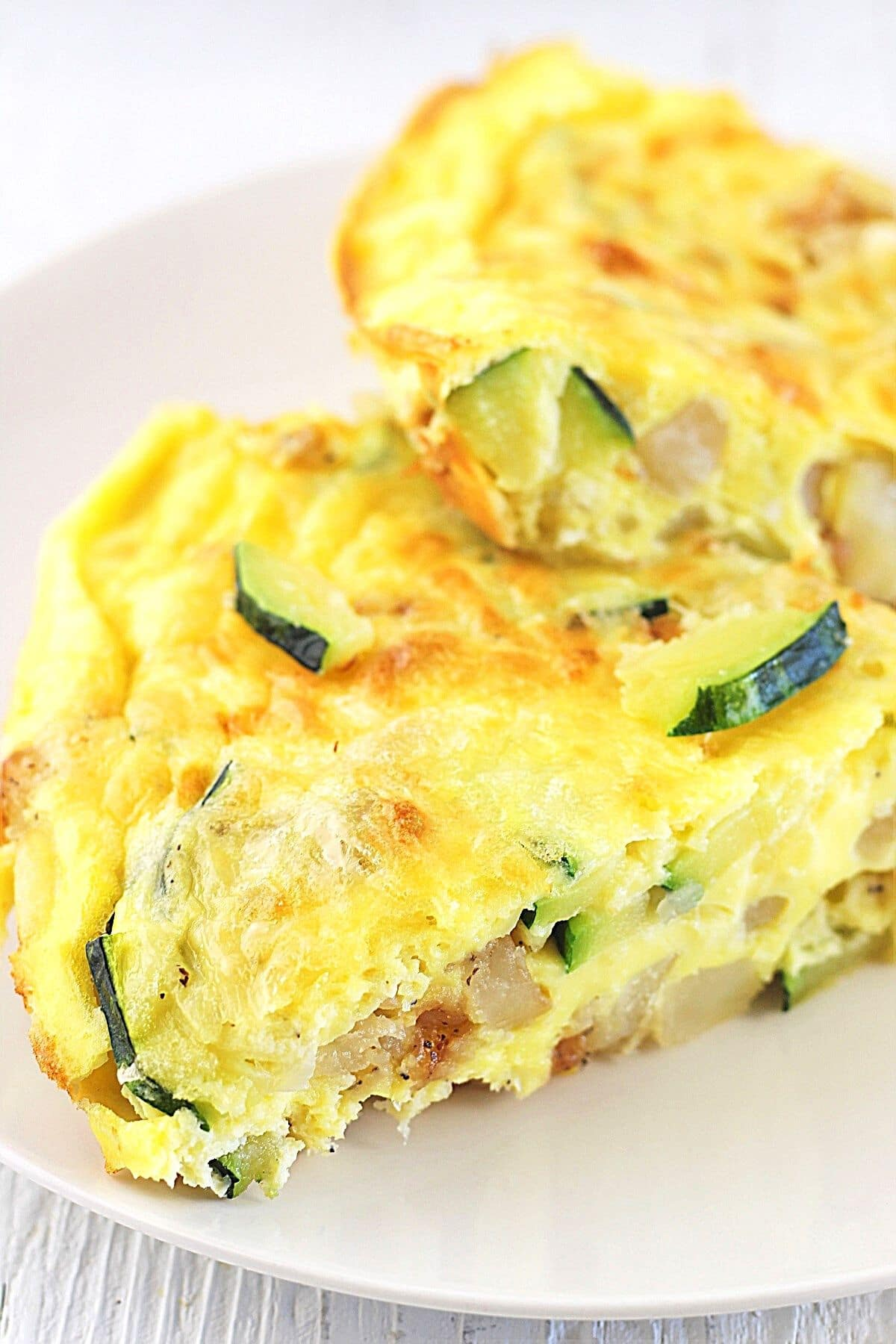 two pieces of zucchini and potato frittata on a white plate