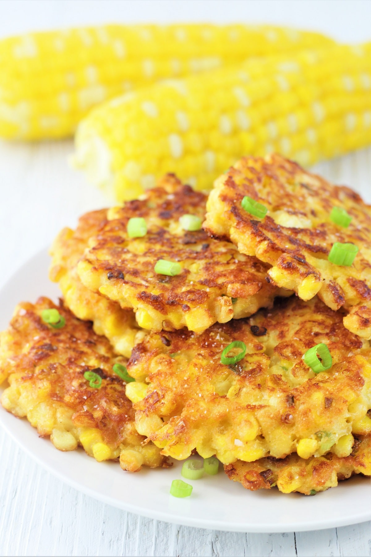 corn fritters on a white plate sprinkled with green onions with two cobs of corn in the background