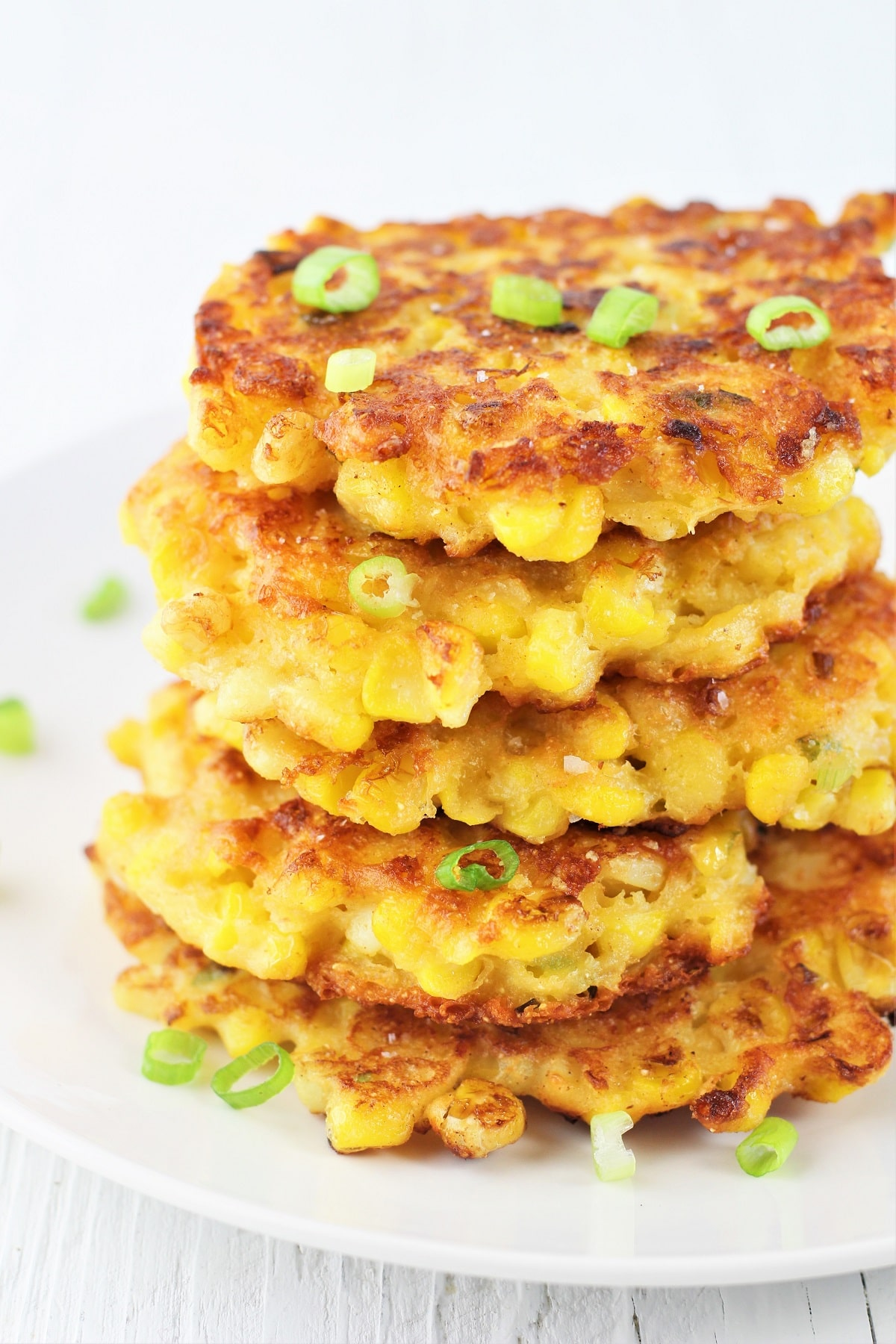 stack of corn fritters on a white plate sprinkled with green onions