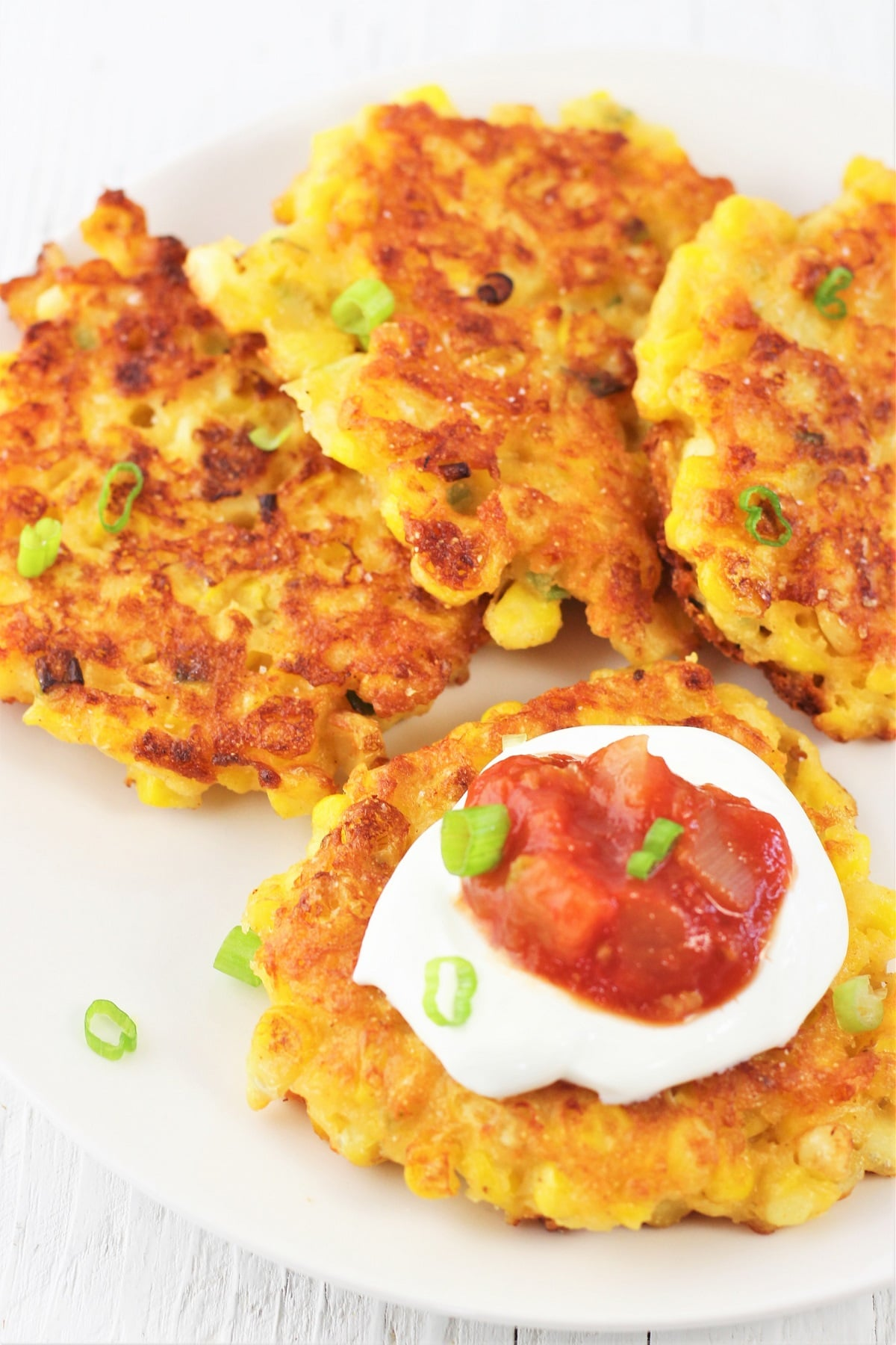 corn fritters on a white plate with one fritter topped with sour cream, salsa, and green onions