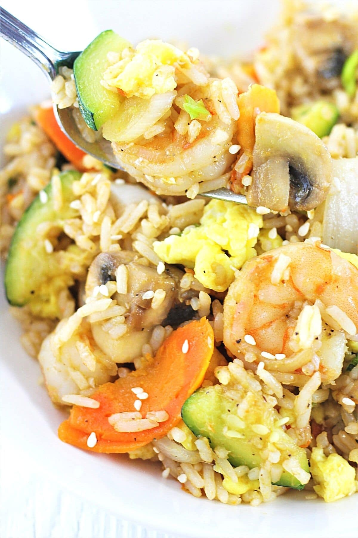 forkful of shrimp fried rice with zucchini and vegetables being taken out of the bowl