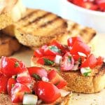 bruschetta with a text overlay that says tomato and basil bruschetta nowcookthis.com