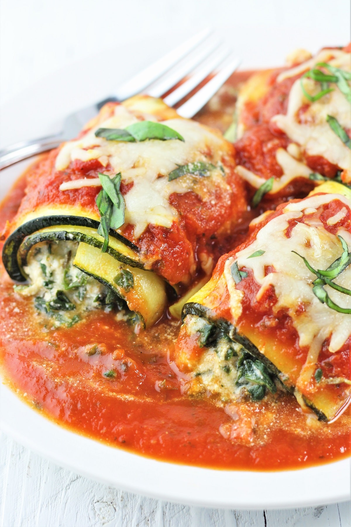 zucchini lasagna roll-ups with spinach and cheese on a white plate with a fork