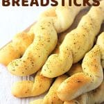 pile of breadsticks with a text overlay that says now cook this homemade garlic and herb breadsticks