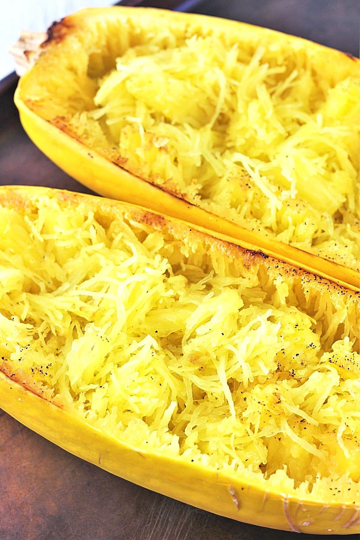 two cooked spaghetti squash halves on a baking sheet