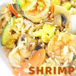 forkful of fried rice with a text overlay that says now cook this shrimp fried rice with zucchini and mushrooms