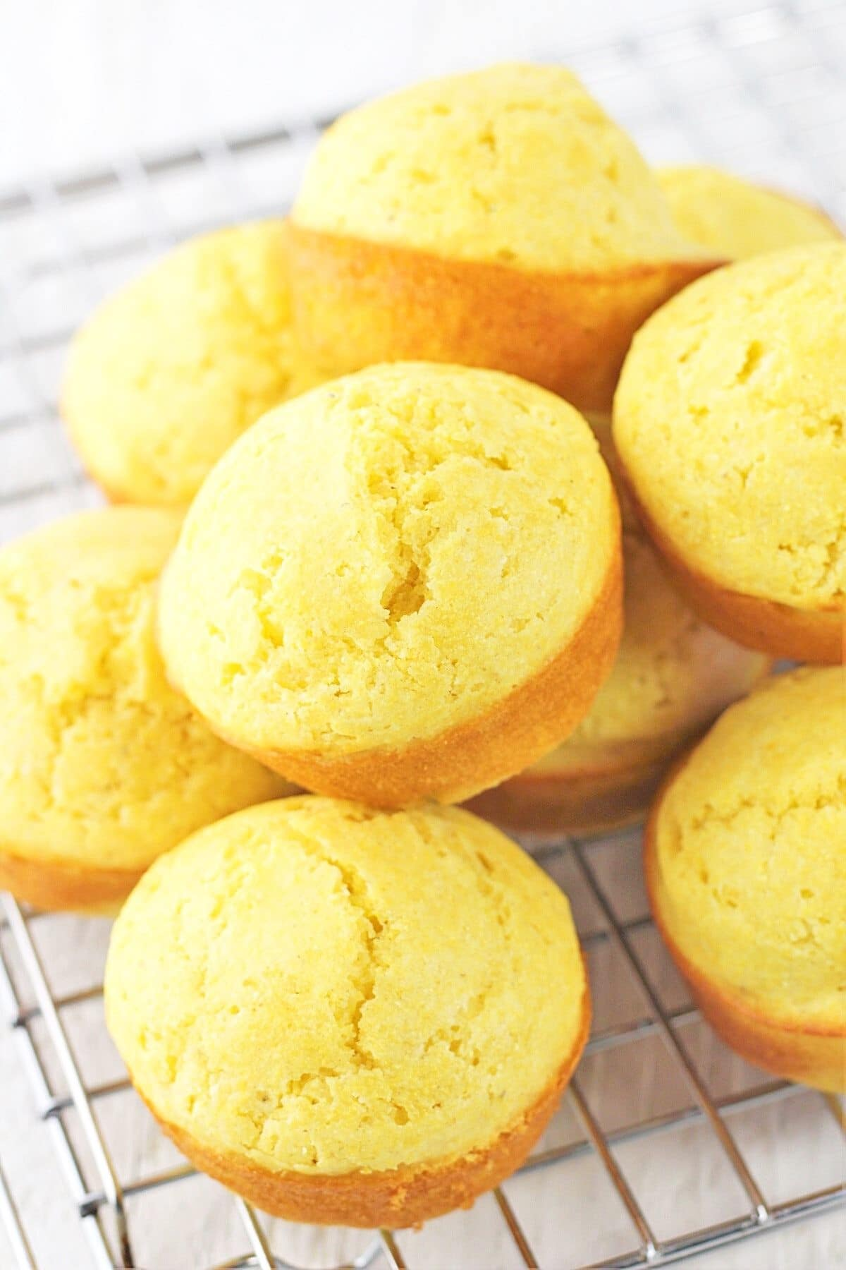 cornbread muffins piled on a wire rack