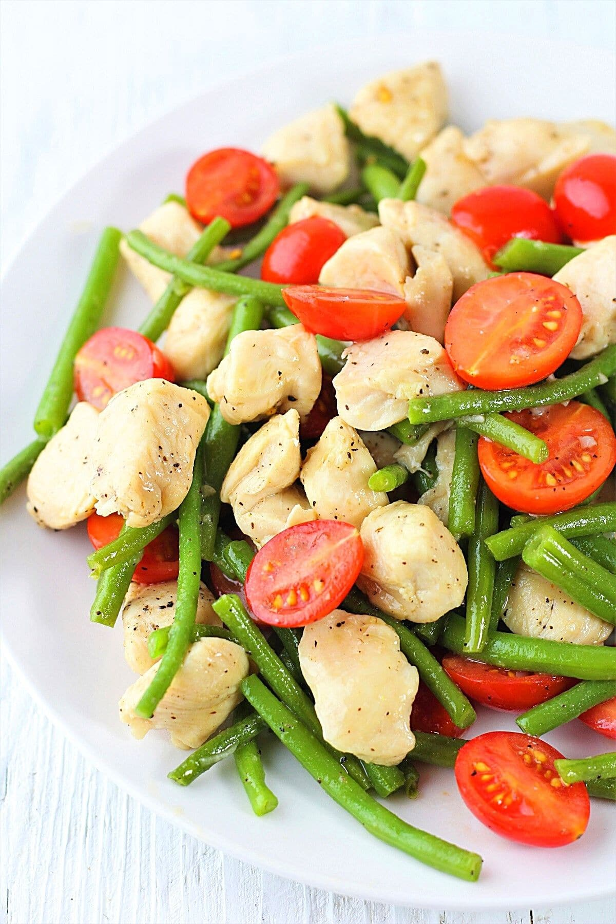 garlic chicken with green beans and tomatoes on a white plate