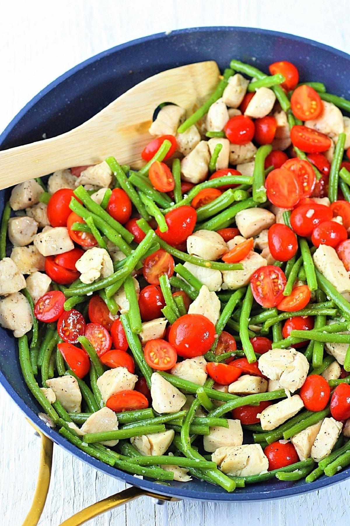 garlic chicken with green beans and tomatoes in a skillet