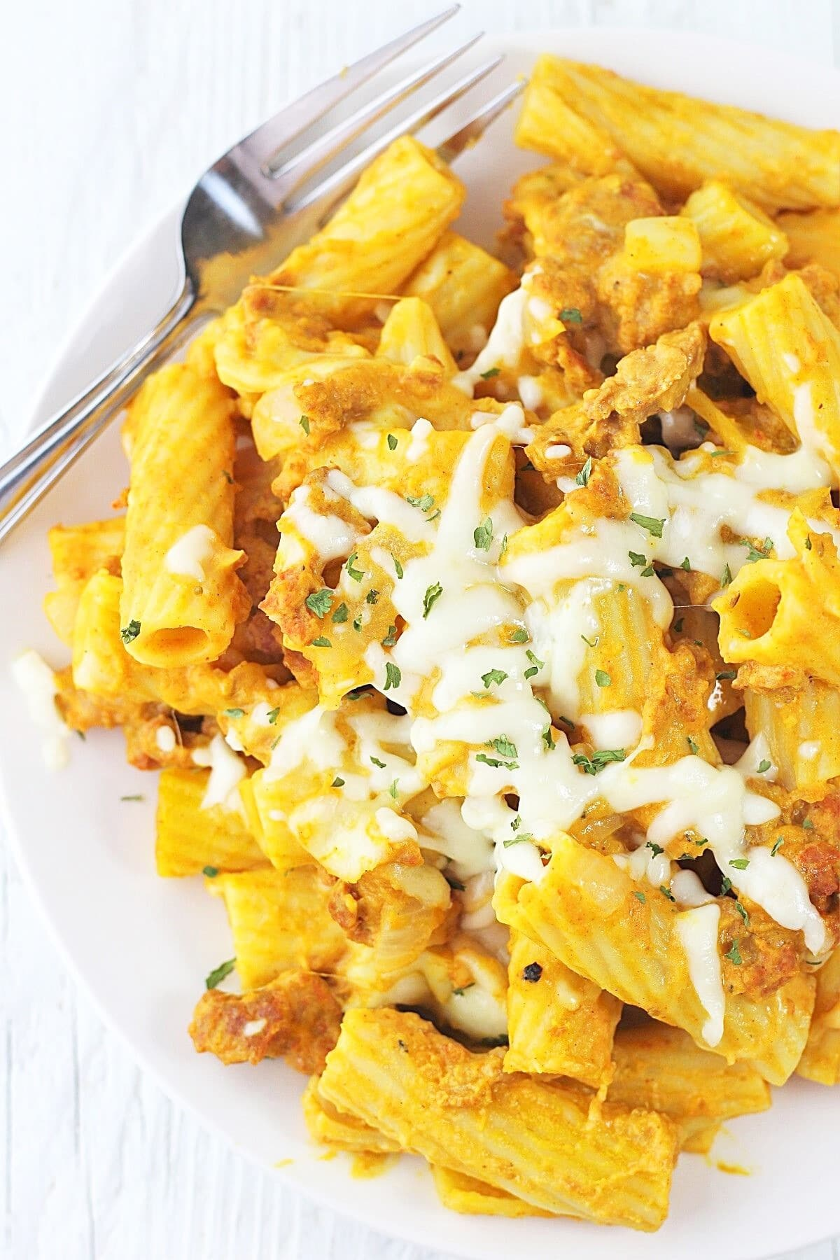 serving of pumpkin and sausage pasta bake on a plate with a fork