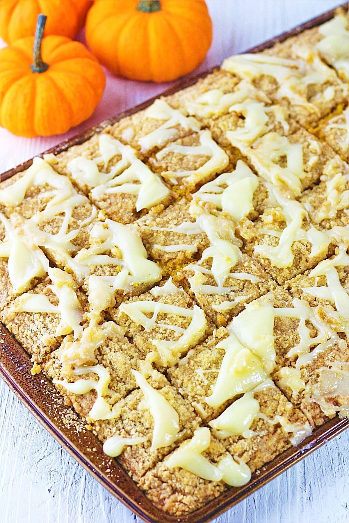 pumpkin streusel sheet cake with cream cheese drizzle and small pumpkins in the background