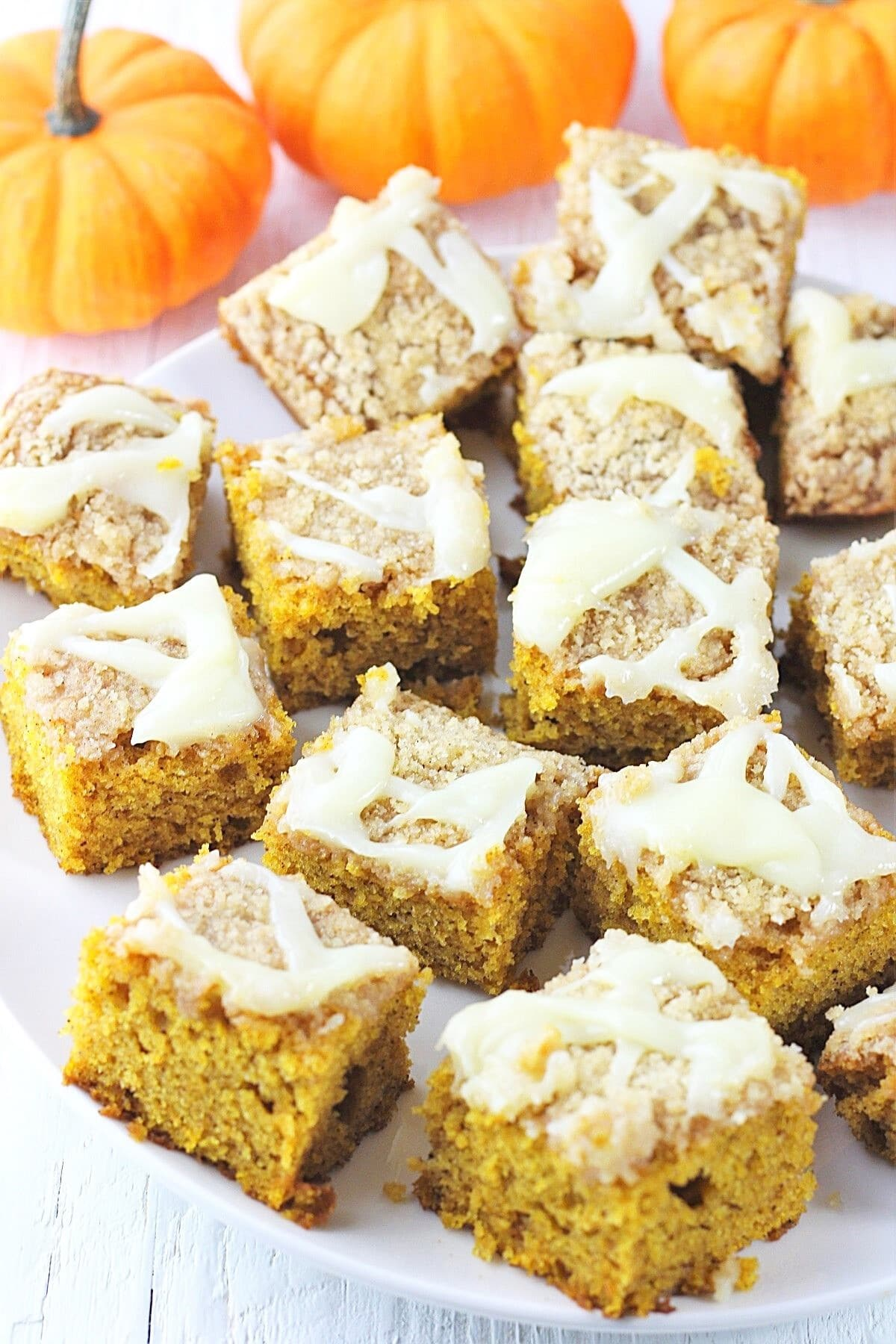 squares of pumpkin streusel sheet cake on a white plate with small pumpkins in the background