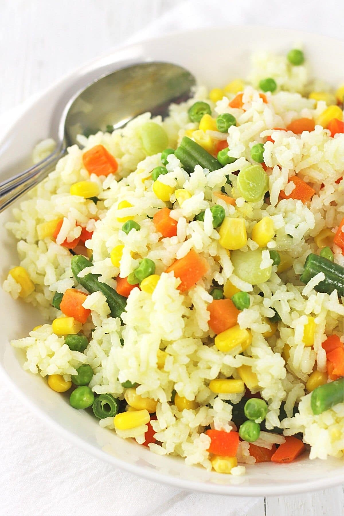 bowl of rice with mixed vegetables with a spoon