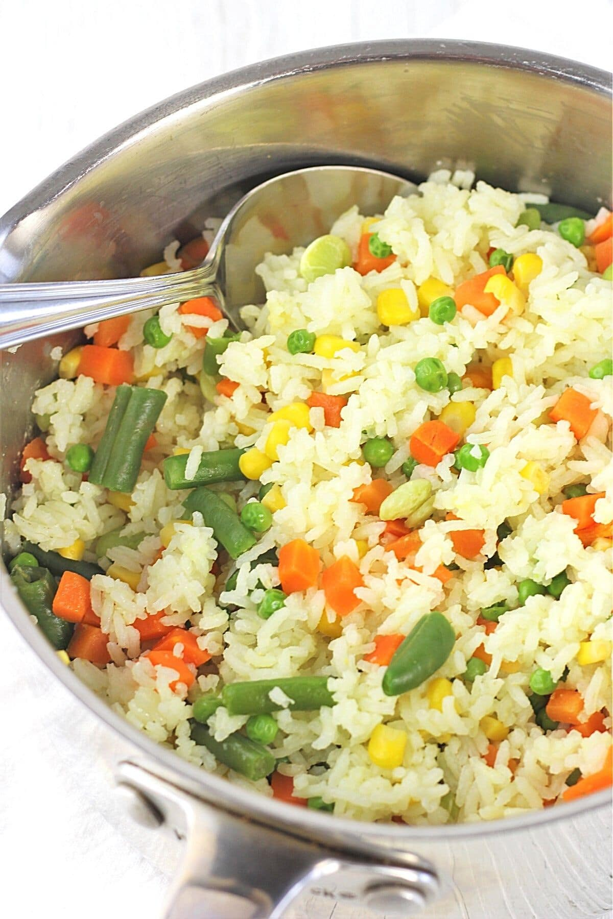 pot of rice with mixed vegetables with a spoon