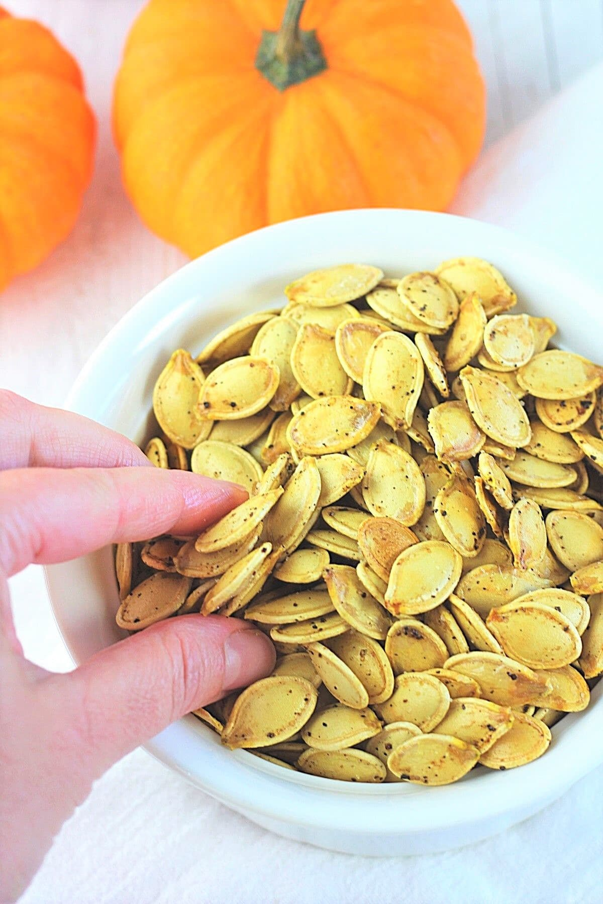 hand reaching into a bowl of roasted pumpkin seeds