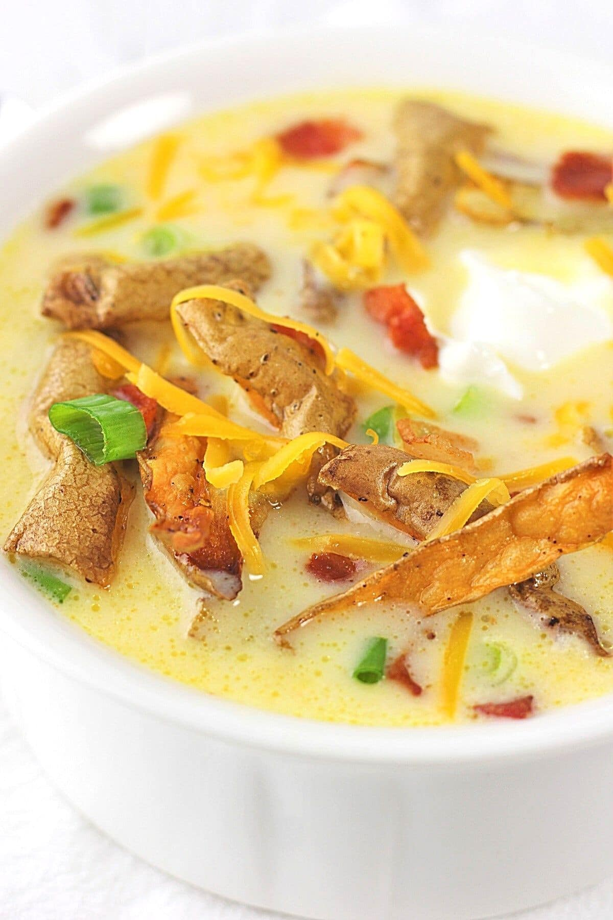 close up of a bowl of cheesy potato soup with crispy potato skins