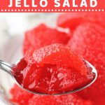 closeup of a spoonful of jello salad with a text overlay that says now cook this cherry applesauce jello salad