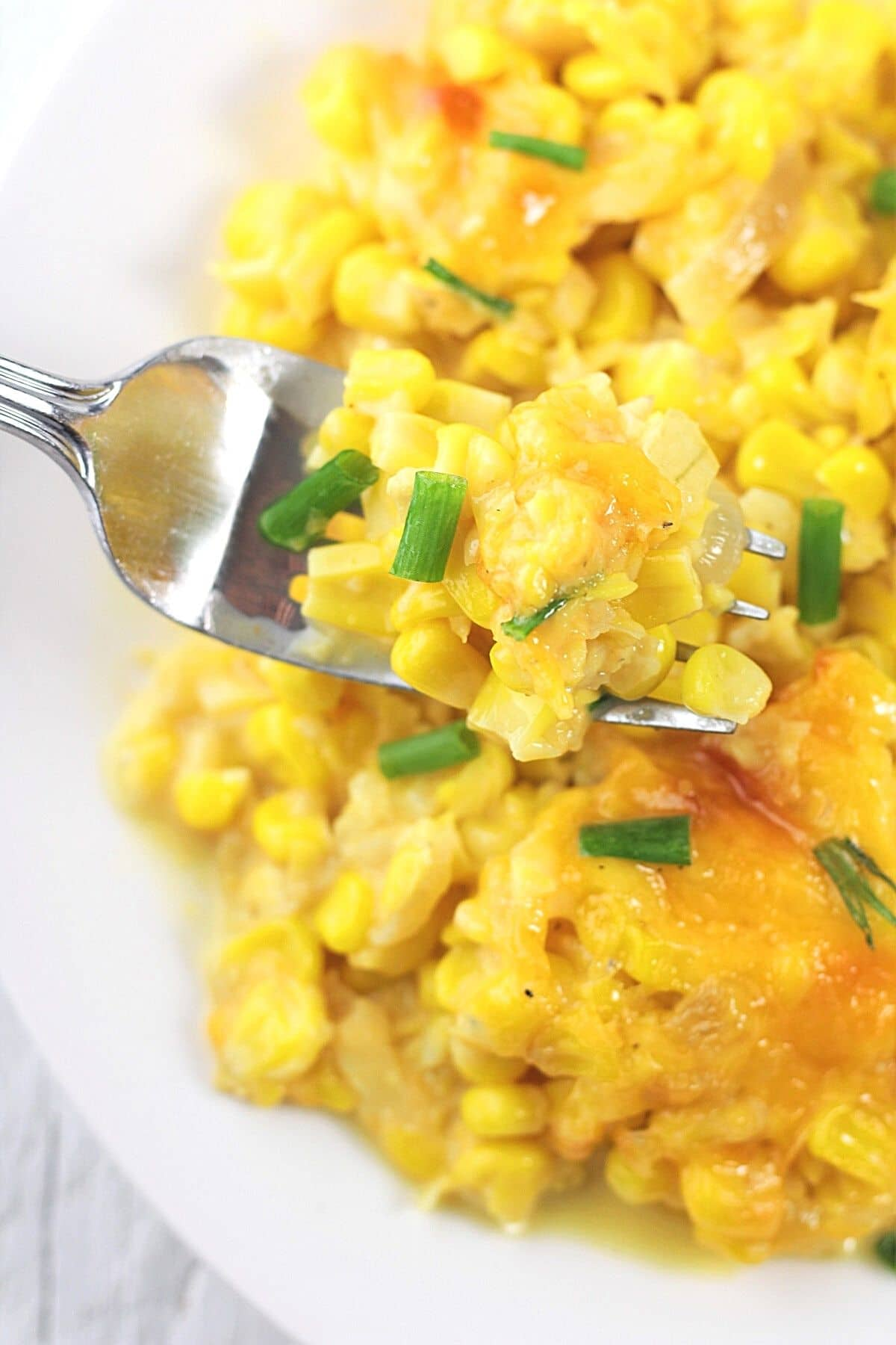close-up of a forkful of cheesy creamed corn