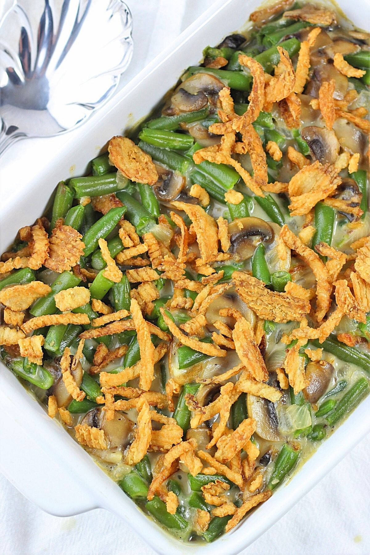 green bean casserole in a baking dish with a serving spoon on the side
