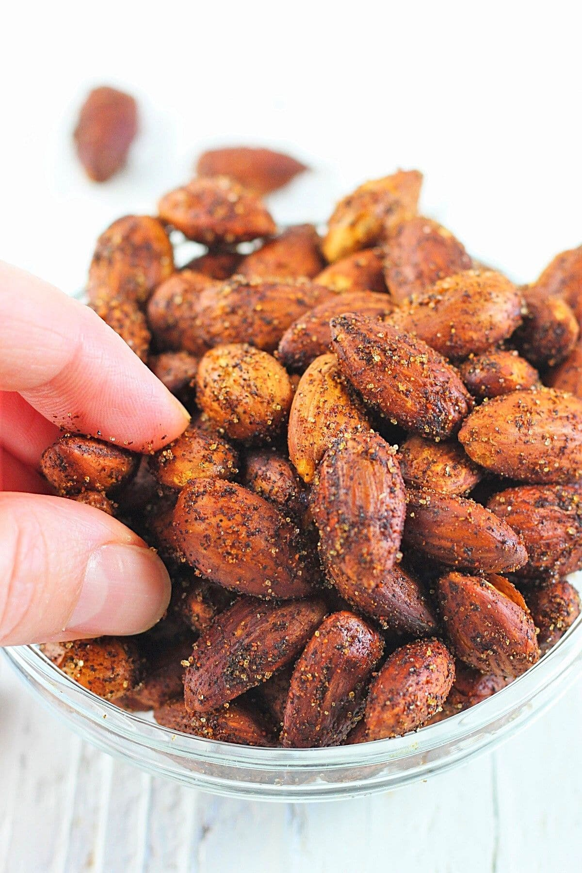 hand reaching into a bowl of smoky roasted almonds