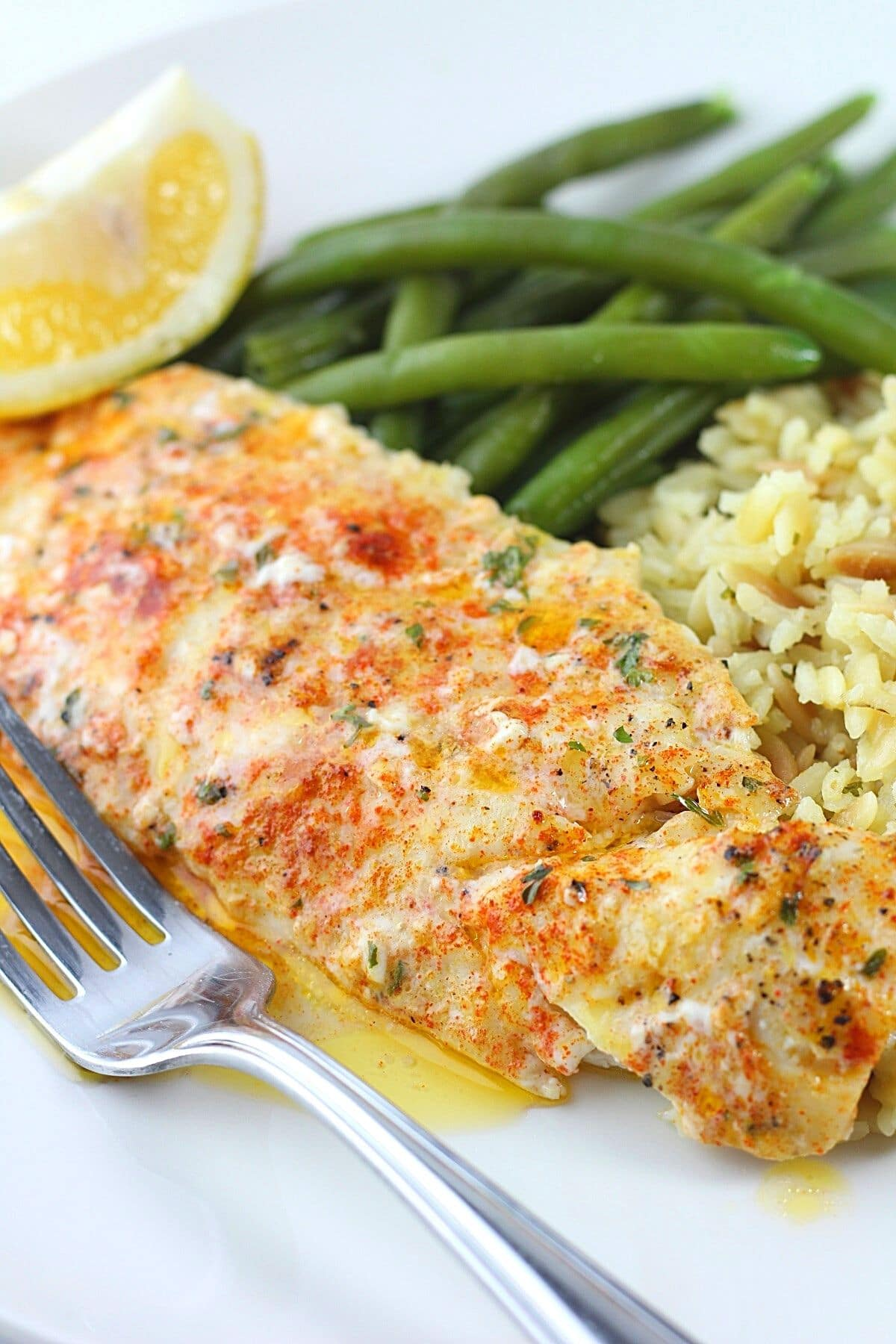 piece of butter-baked haddock on a plate with a fork and rice and green beans
