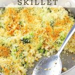 skillet of food with a serving spoon with a text overlay that says cheesy chicken, broccoli and rice skillet nowcookthis.com