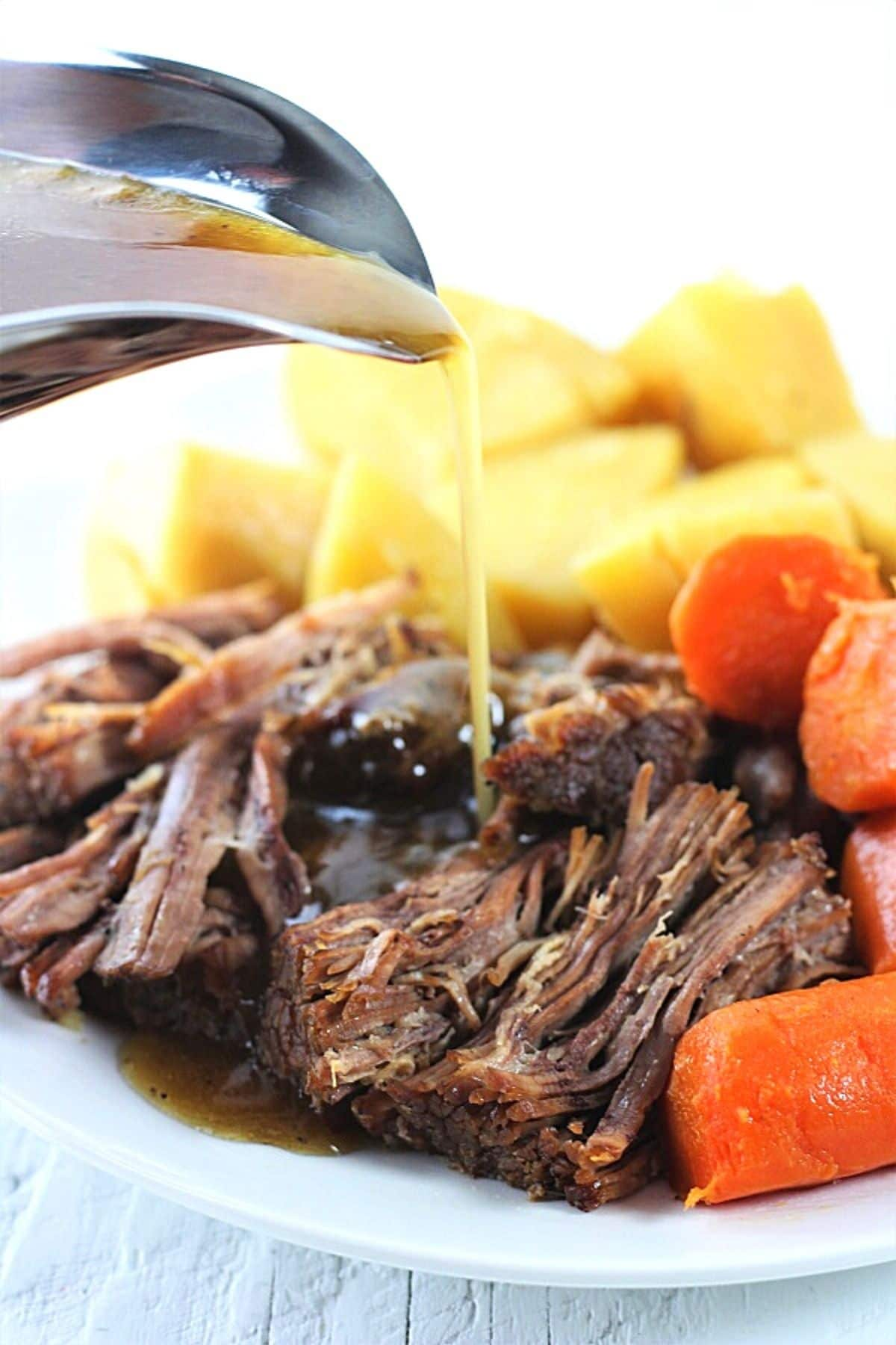 pot roast with vegetables with gravy being poured over the top