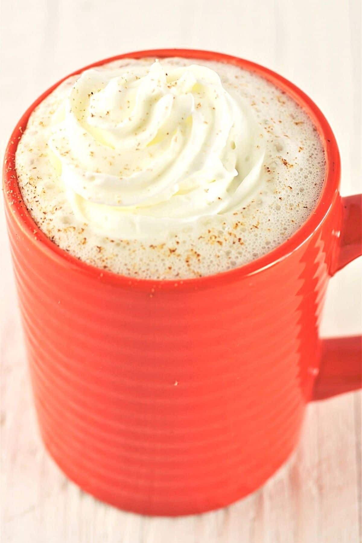 mug of warm vanilla milk bedtime drink with whipped cream on top