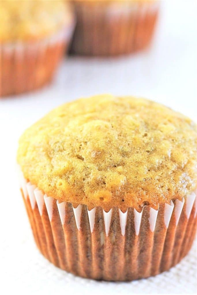 close-up of a single banana bread muffin with more muffins in the background