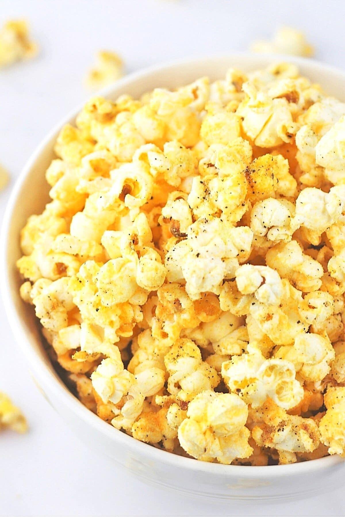 white bowl full of cheesy garlic pepper popcorn