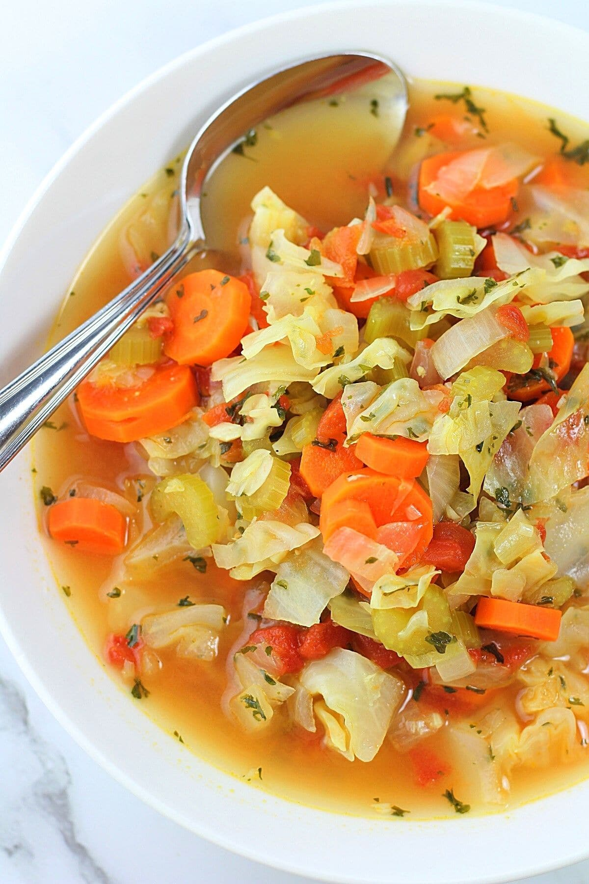 low-calorie cabbage soup in a white bowl with a spoon