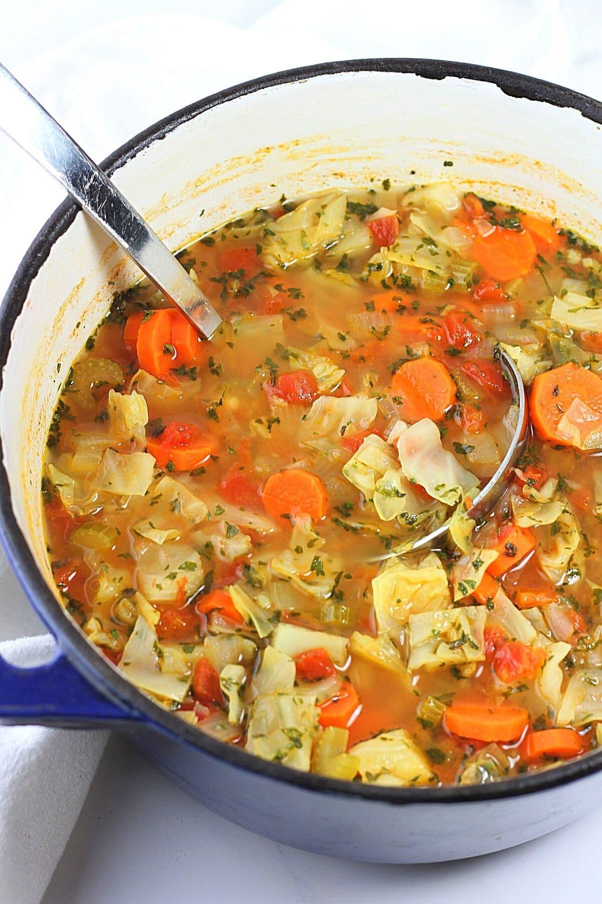 pot of low-calorie cabbage soup with a ladle