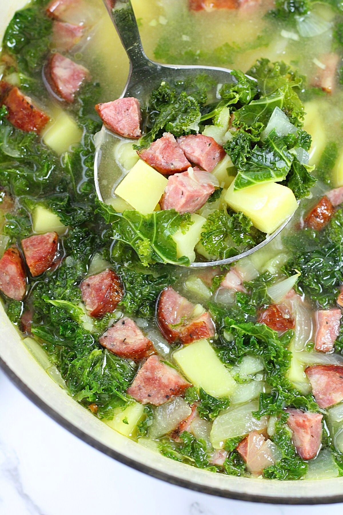 ladle of caldo verde-style soup over a pot of soup