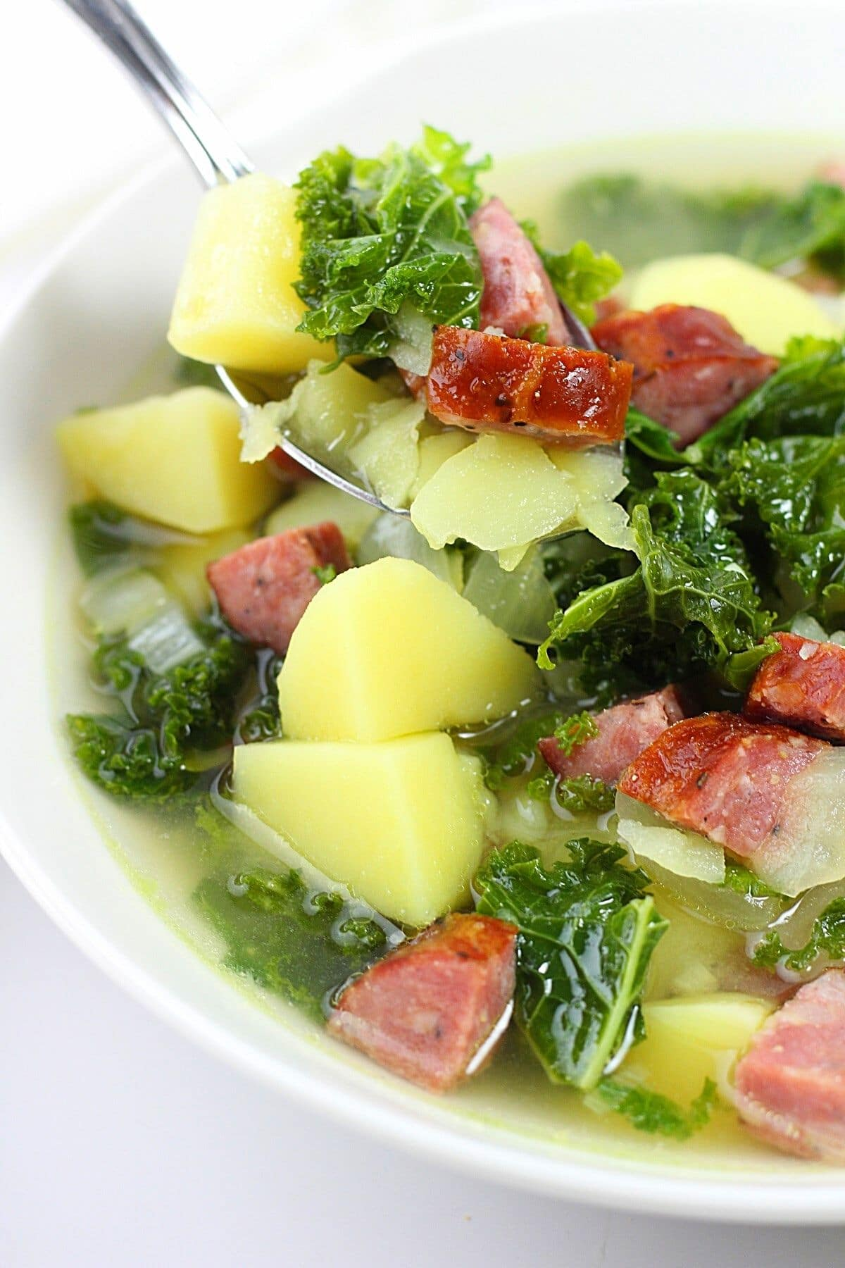 spoonful of caldo verde-style soup over a bowl of soup