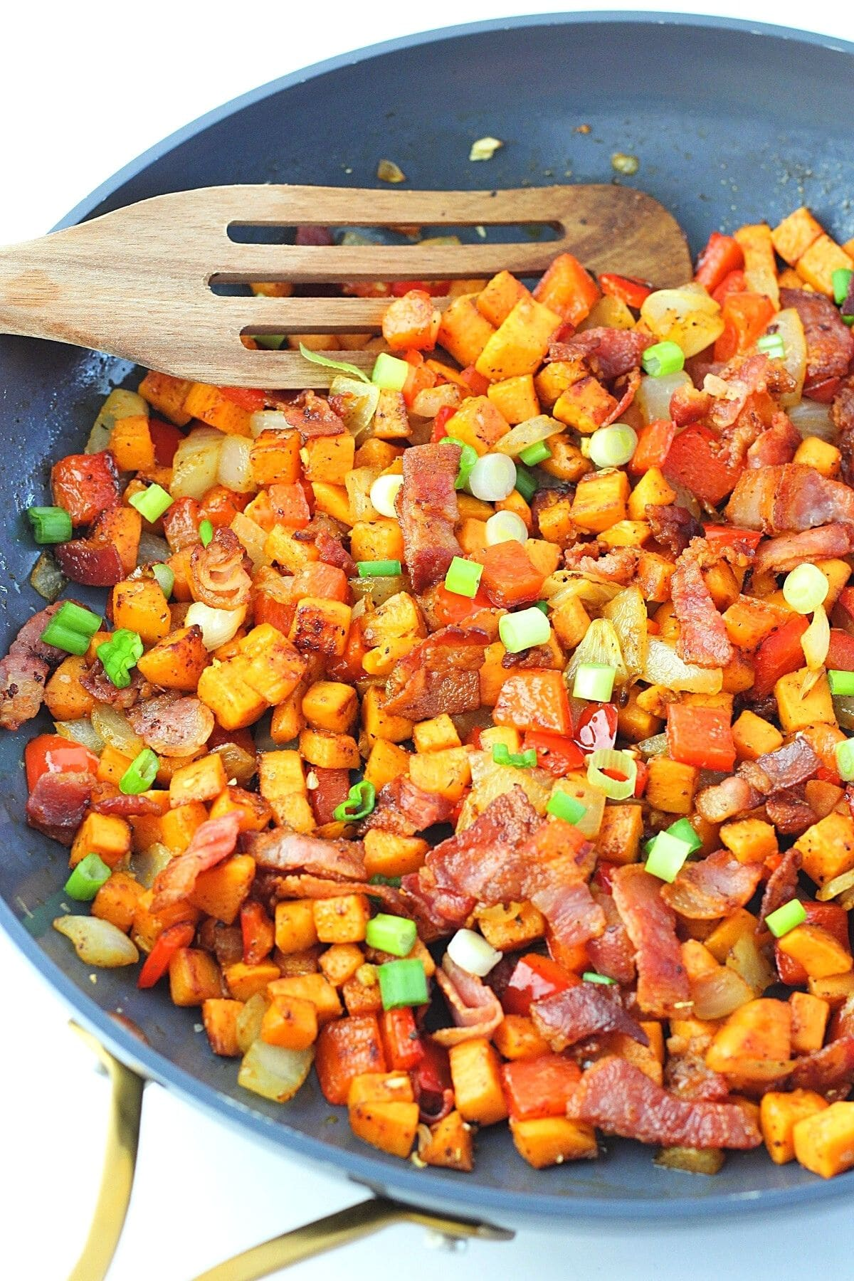 sweet potato hash with bacon in a skillet with a wooden spatula