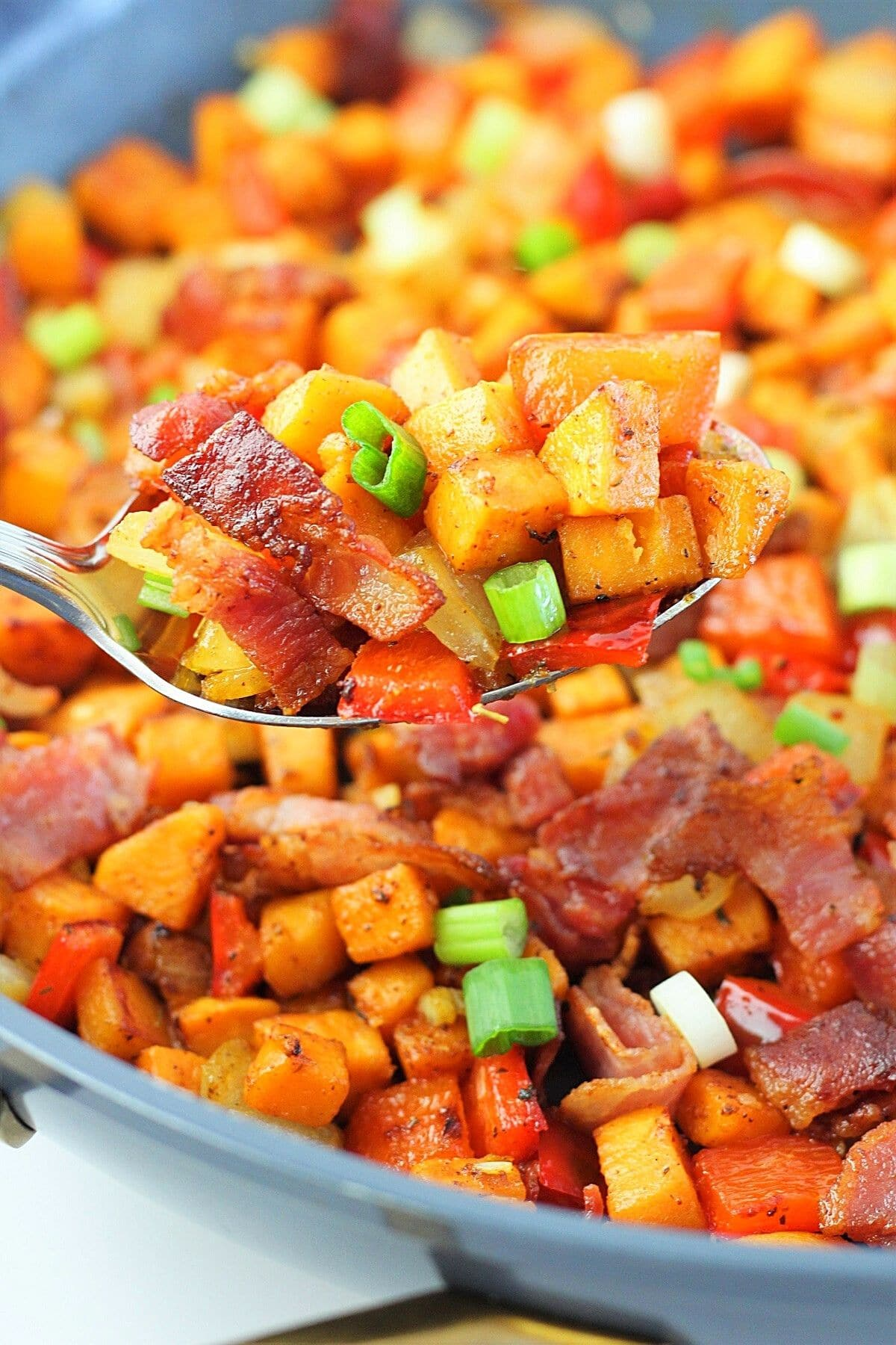 close-up of a spoonful of sweet potato hash with bacon being taken out of the pan