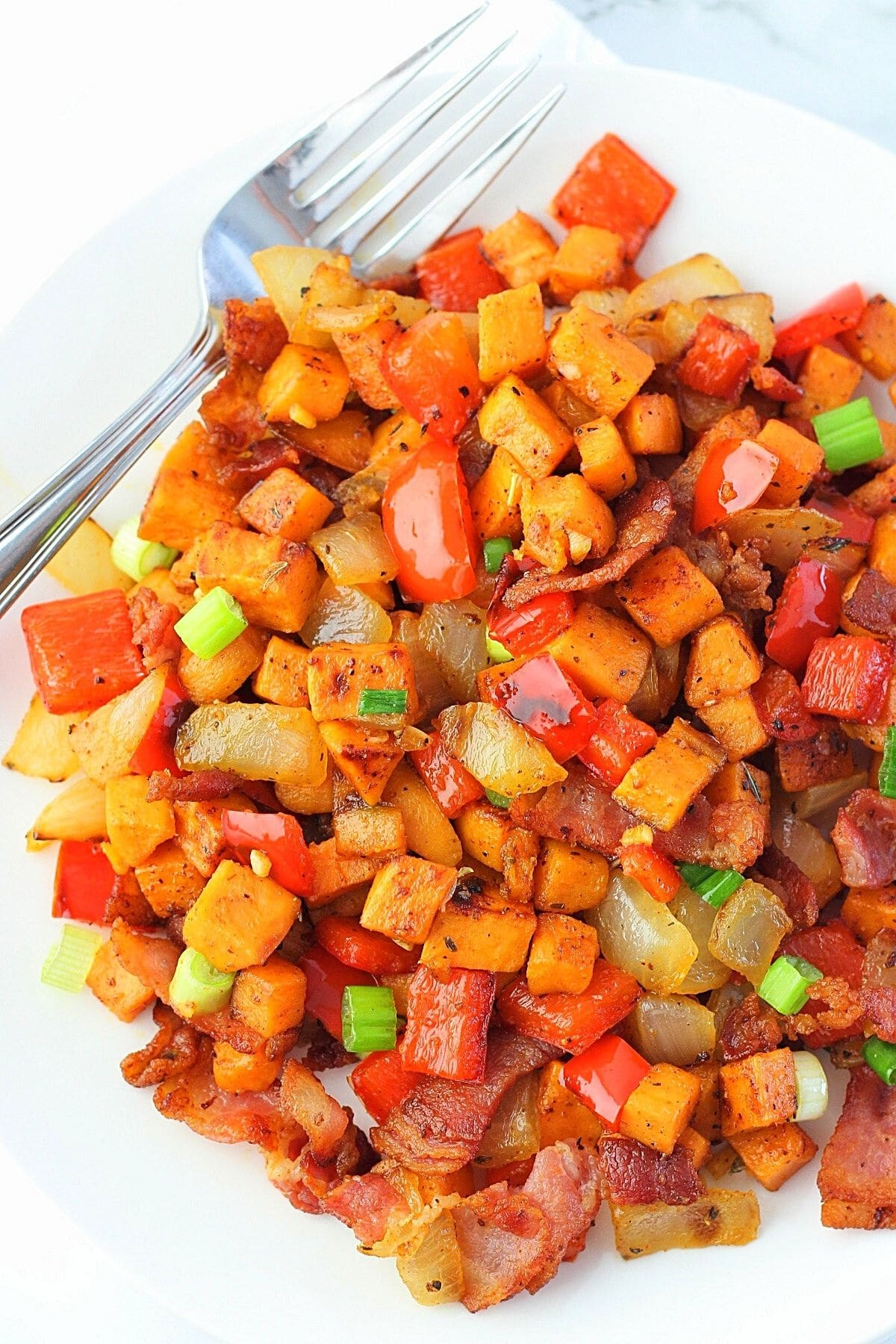 sweet potato hash with bacon on a white plate with a fork