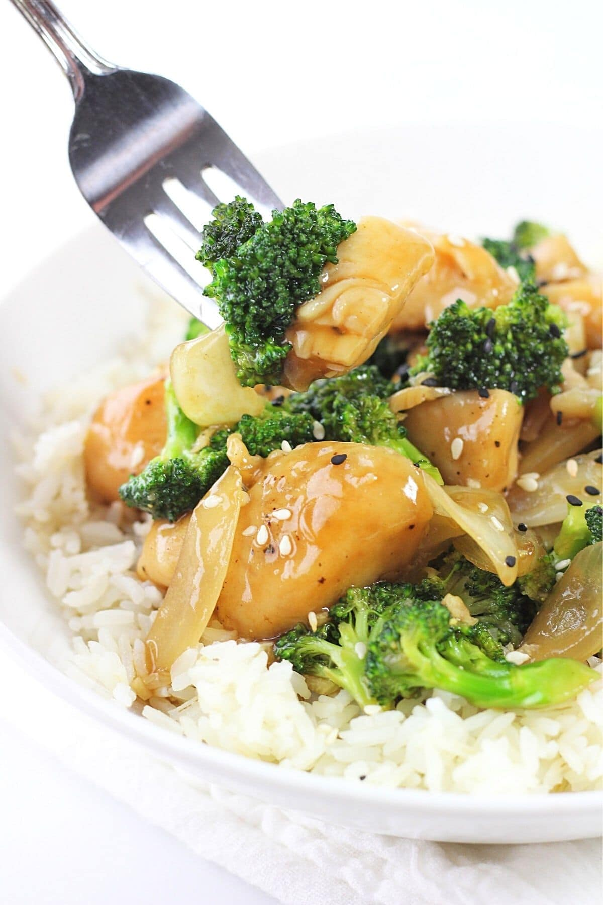 forkful of chinese chicken and broccoli stir-fry being taken from the bowl