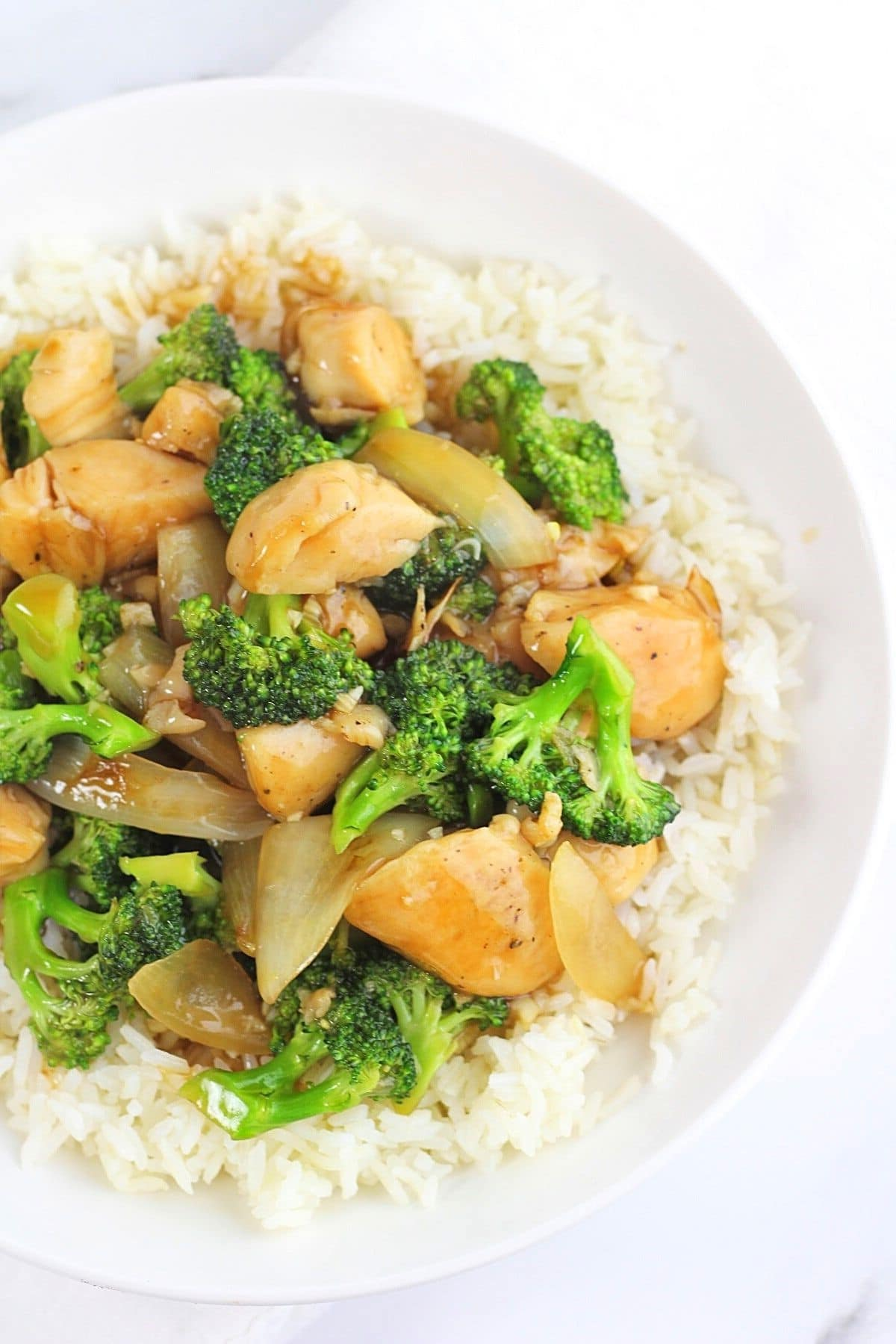 chinese chicken and broccoli stir-fry over white rice in a bowl